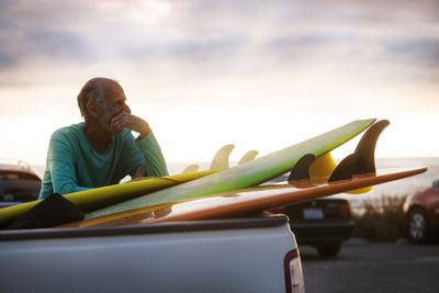A boomer leans on a stack of surfboards in the back of a pickup after a long day of surfing and wonders if he should have saved more and surfed less.