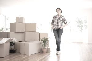 woman standing in front of pack moving boxes