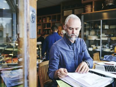 A small business owner sitting in a cafe works on accounting books