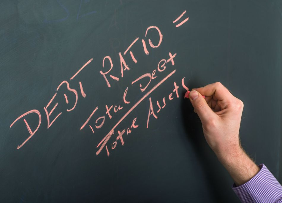 debt ratio on blackboard with hand