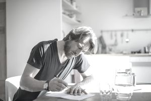 Bearded man filling out paperwork at dining room table