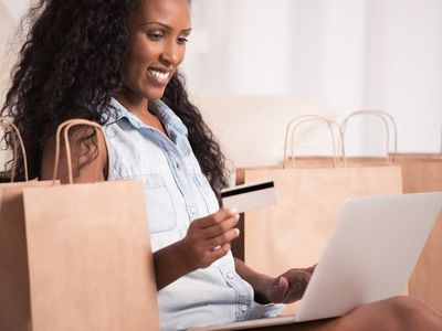 Smiling woman using laptop holds magnetic stripe credit card