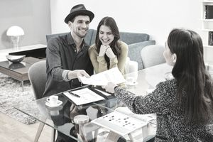 A smiling young couple signs paperwork on a glass-topped desk.