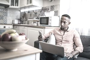 A man looks at his phone while working
