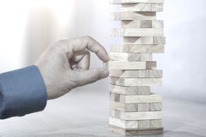 Hand removing block from Jenga game signifying planning, risk and strategy in business