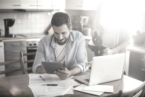 Man in his 20s creating savings goals with a laptop and scattered paperwork