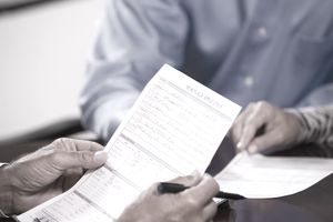Close up of man filling out a loan form.