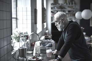 Tired looking senior man leaning on kitchen counter with sports drink.