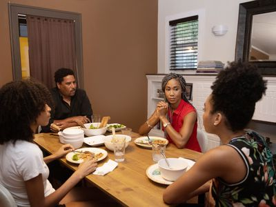 A family sits and talks around the dinner table