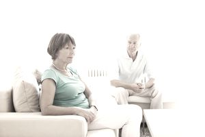 Older male-female couple sitting away from each other on a tan couch