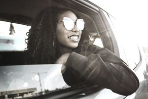 A young woman wearing sunglasses looks out her open driver's side window, smiling