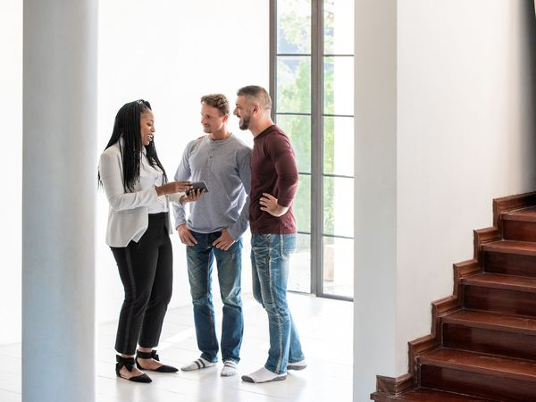 Female real estate agent working with two men looking at a home for sale.