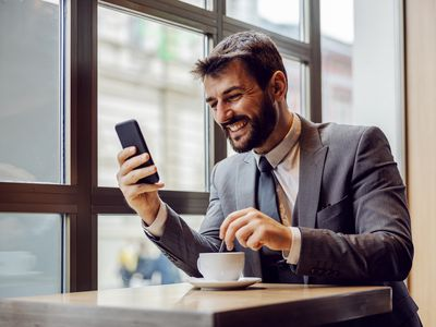 An investor tracks the Dow 30 on his phone in a coffee shop..