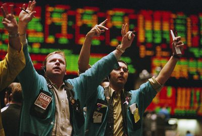 Traders waving arms to on the stock exchange floor