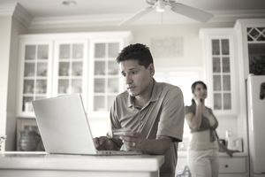 a man holding a credit card and using a laptop
