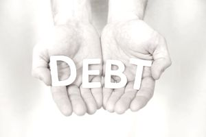 a man's cupped hands hold letters spelling the word debt