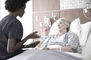 Nurse talking to senior woman in hospital bed