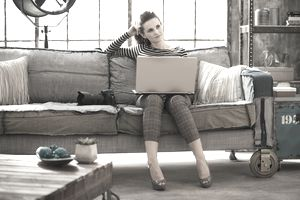 Woman sitting on sofa in new home thinking about the photos of her old home on a realtor's site.