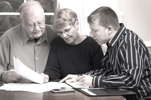 Senior couple talking to a financial advisor about inheritance tax their beneficiaries may have to pay.