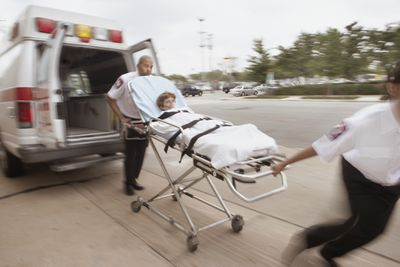 Blurred shot of emergency medical technicians wheeling a gurney with a patient on it away from ambulance