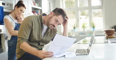 Man consults financial paperwork with wife and baby looking on