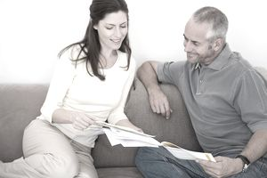 Couple sitting on a sofa looking at paperwork