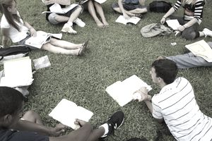 a circle of college students studying outside on a grassy area