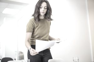 Young businesswoman contemplating papers in a bright office