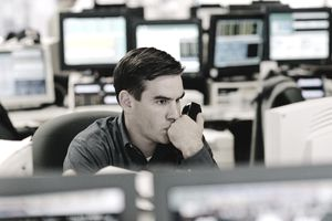 Stock trader watches computer screen while holding phone