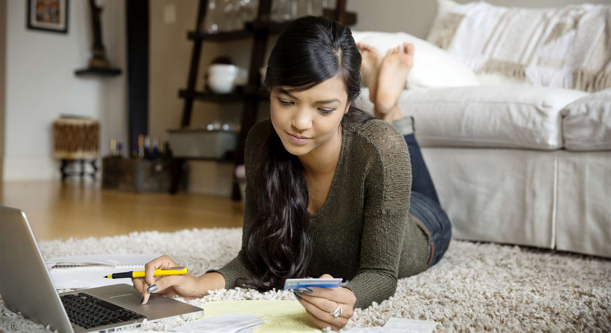 Young woman using credit card to pay online bills