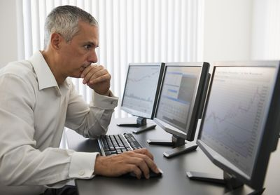 Silver-haired man day trading on a computer in front of three monitors