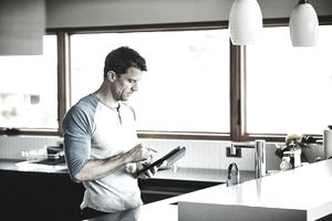 Man working on digital tablet in kitchen of home