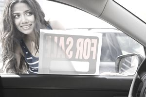 Middle Eastern woman looking at car for sale.