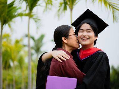 Older Woman Hugging Young Woman Graduate With Black Cap and Gown On