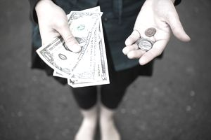 Woman holding cash and coins in her hands.