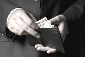 Closeup of a man's hands taking money out of a billfold
