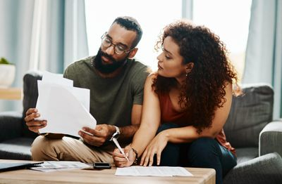 Couple seated on couch reviews their investments