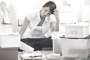 Woman looking at paperwork, files, and file boxes on her living room floor