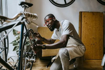 A business owner repairs a bicycle.