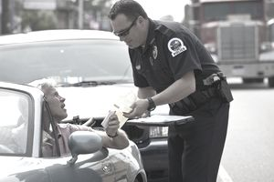 Senior citizen receives traffic citation from policeman for unsafe driving.