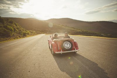 Couple in vintage car on wide road at sunset