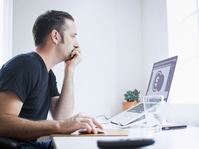 Man at desk looking at a computer screen with a dollar sign on it