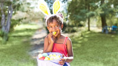 A young girl wearing Easter bunny ears bites a Peep while holding a basket of Easter eggs in a park