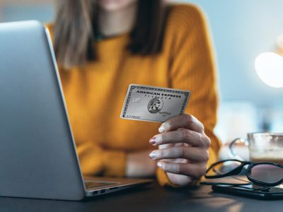 Woman holding American Express Platinum Card while sitting in front of a laptop.