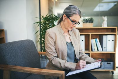Woman in blazer and glasses filling out paperwork on clipboard in office