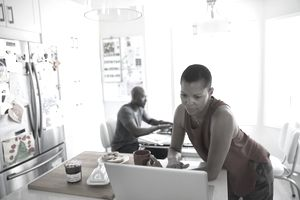 A couple working separately on laptops in a kitchen