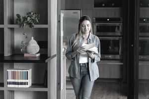 woman walking at her apartment while opening letters
