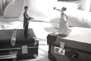 bride and groom figurines on separate luggage
