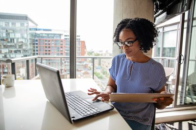 Woman in High-Rise Working at Laptop