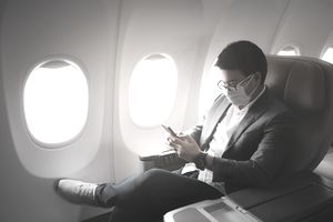 Young Asian businessman wearing a protective face mask and suit sits in business first class seat using a smartphone.